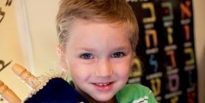 Little boy holding torah scroll