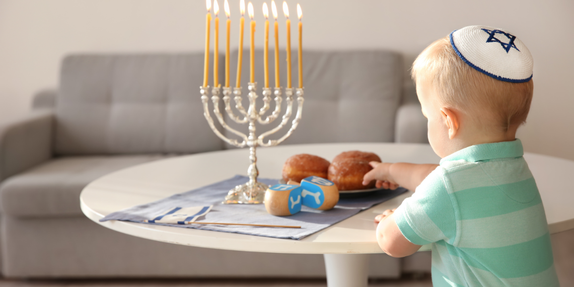 Little boy reaching for jelly rolls with hanukkiah on a table