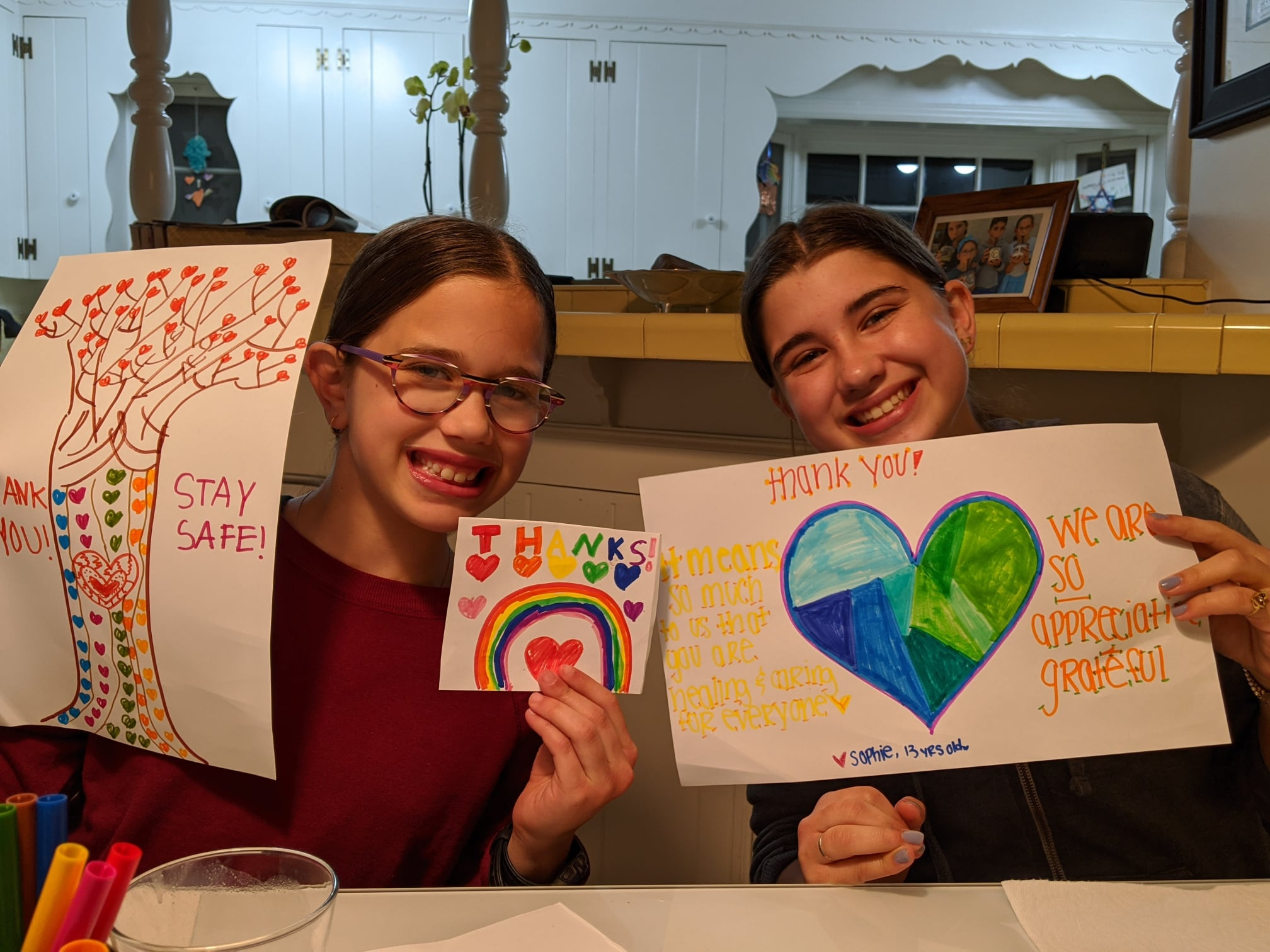 Two girls with posters they created doing acts of kindness