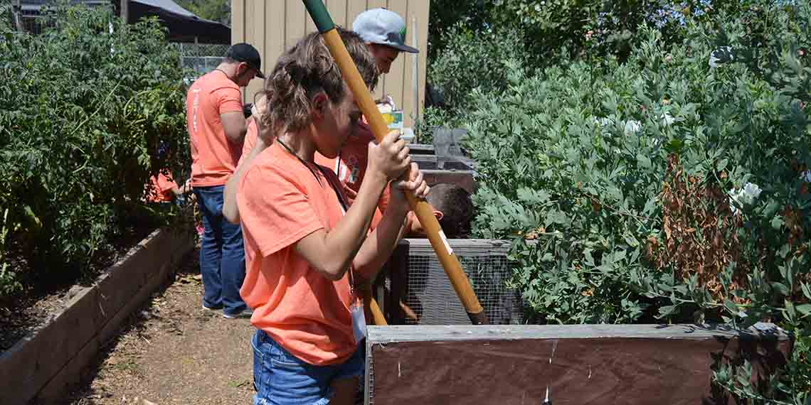 Teen service learning volunteers tilling the soil