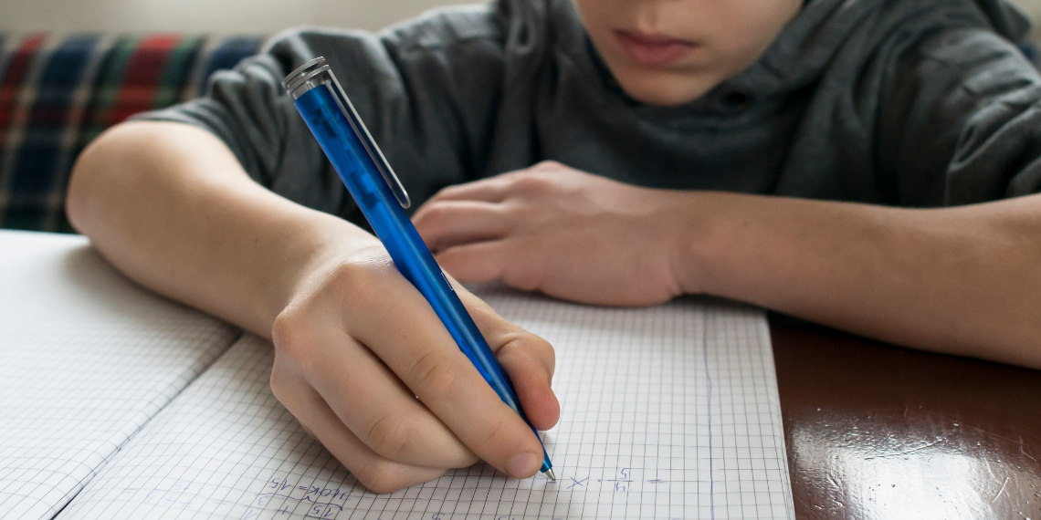 close up of young boy writing math into a notepad