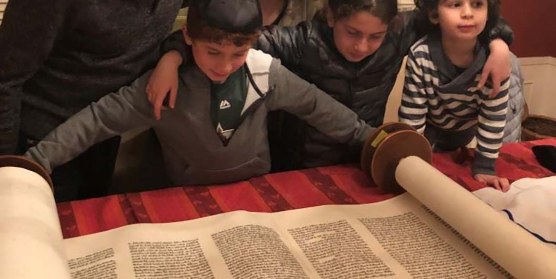 children looking at the Torah